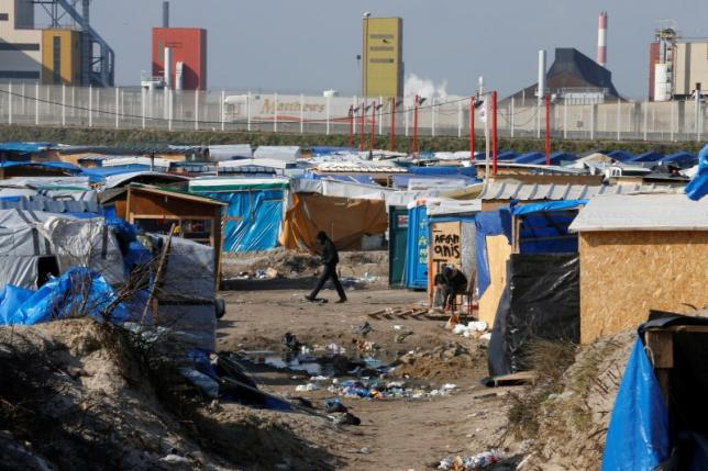 "A migrant walks past makeshift shelters in the northern area on the final day of the dismantlement of the southern part of the camp called the 'Jungle"" in Calais"